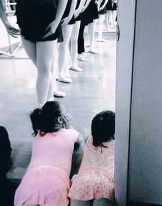 Little girls watch big girls dance.